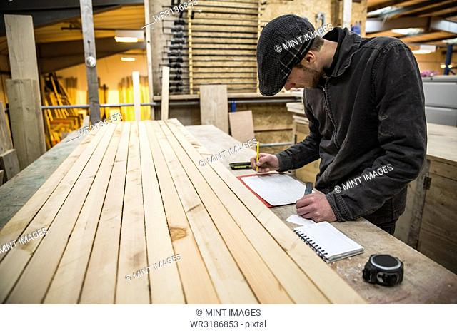 Man wearing flat cap standing at a workbench with wooden planks in a warehouse, holding ruler, writing measurements on piece of paper