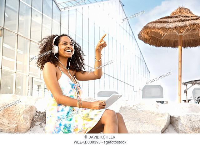 Happy young woman with headphones and digital tablet outdoors