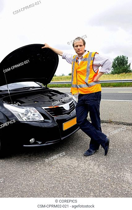 Motorist wearing a safety vest posing in front of the open hood of his broken down car on the shoulder of a motorway, waiting for assistance