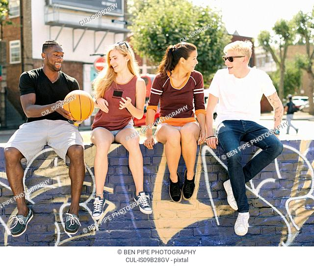 Male and female basketball friends sitting chatting in city skatepark