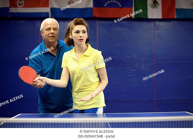 Table tennis coach teaching student to play