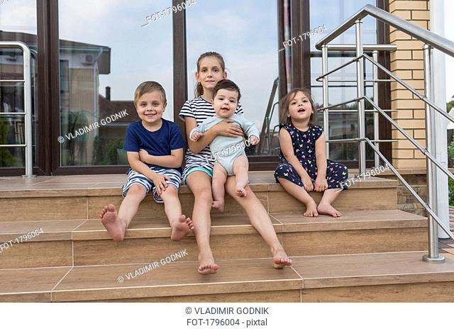 Portrait barefoot brothers and sisters sitting on patio steps