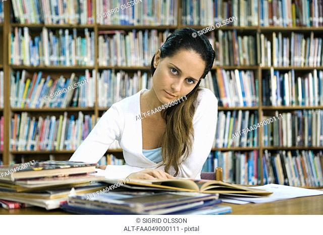 Female college student reading book at table in library, looking at camera
