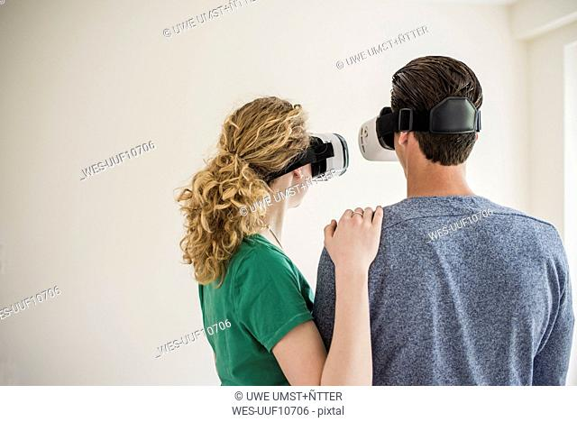 Young couple in empty apartment wearing VR glasses