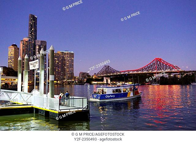 People waiting at Eagle Street ferry wharf while a ferry leaves, with Brisbane city skyline, Australia