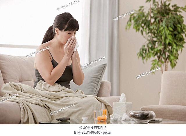 Sick Asian woman sitting on sofa blowing her nose