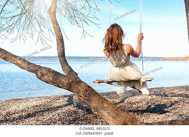 Rear view of woman on rope swing by ocean