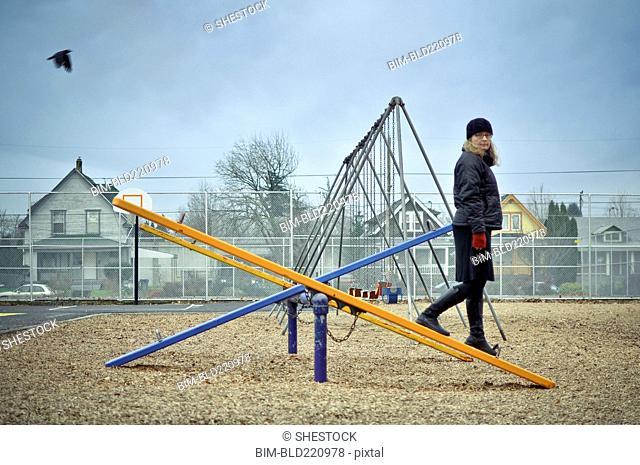 Caucasian woman walking on playground seesaw