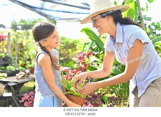 Smiling woman and girl with potted plant in sunny greenhouse