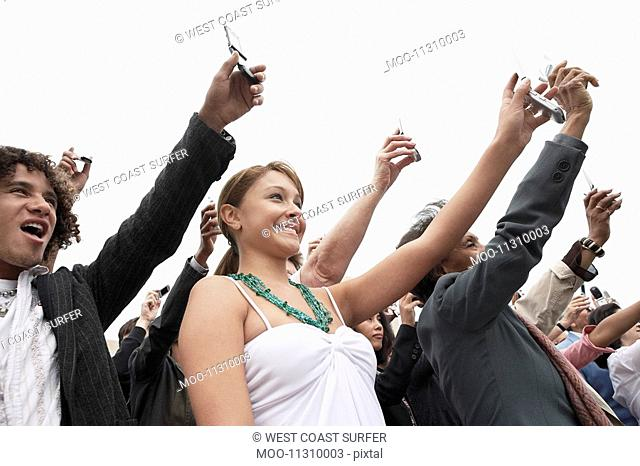 Crowd holding up cell phones half length