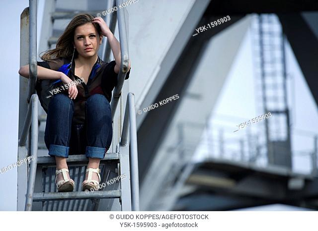 Rotterdam, Netherlands. Young, fashionable woman from Afghanistan, living in asylum in the Netherlands, posing near the docks of Rotterdam harbor