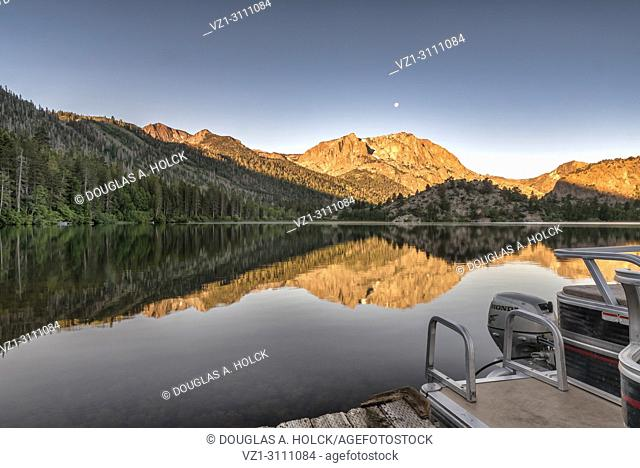 A full moon sets and the sun rises above Carson Peak and Gull Lake in the Eastern Sierra Nevada Mountians