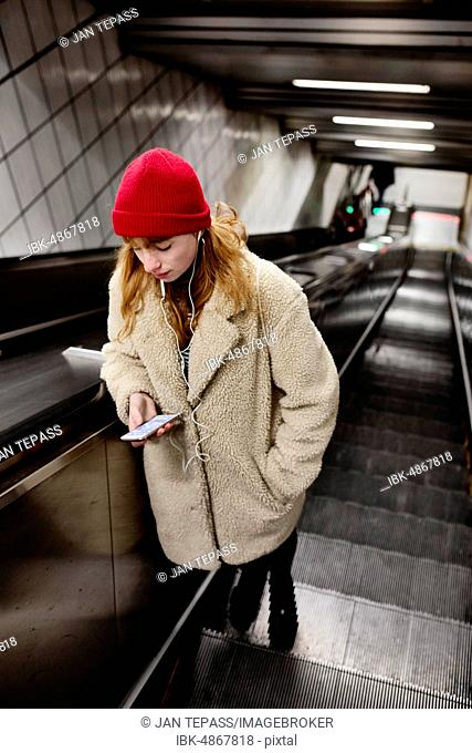 Girl, teenager, with smartphone in hand and headphones in her ear on escalator of a subway station, Cologne, North Rhine-Westphalia, Germany