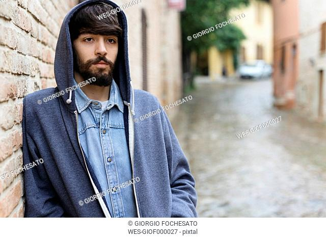 Italy, San Gimignano, portrait of pensive young man wearing hooded jacket