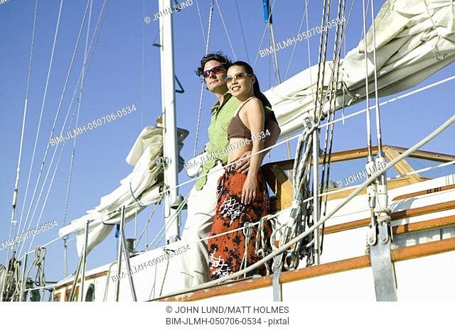 Low angle view of couple on sailboat