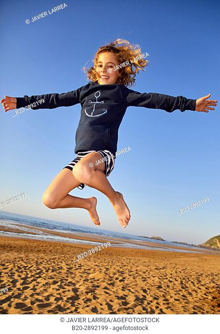 Girl jumping on the beach, Zarautz, Gipuzkoa, Basque Country, Spain, Europe
