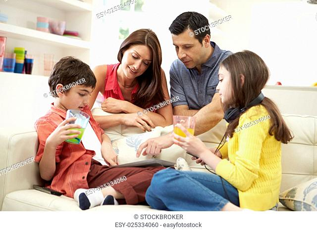 Family Playing With Digital Tablet And MP3 Player