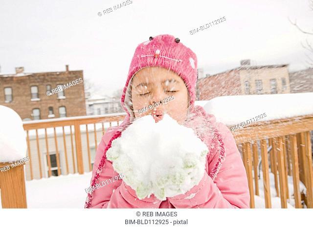 Hispanic girl playing with snowball