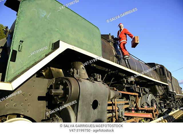 Man disguised as Santa Claus in a steam train locomotive