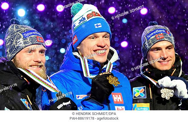 Iivo Niskanen from Finland (M.) takes gold ahead of Martin Johnsrud Sundby (l.) from Norway and Niklas Dyrhaug from Norway at the medal ceremony after the men's...