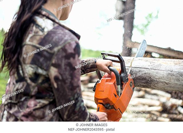 Woman using chainsaw