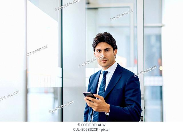 Businessman using smartphone in office building