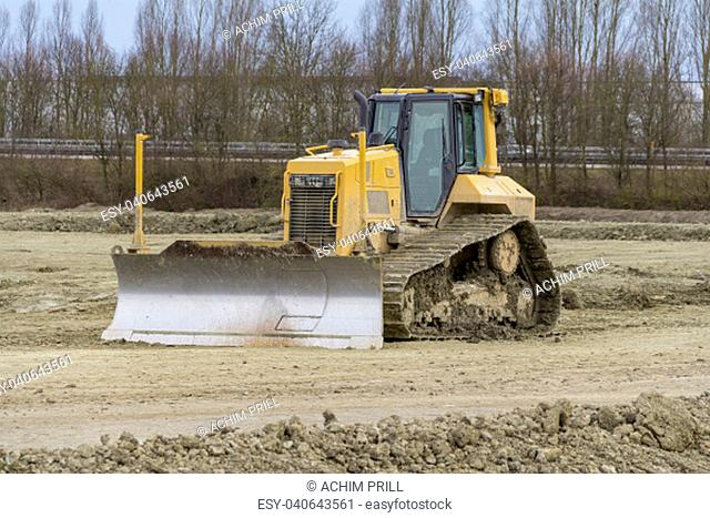 yellow bulldozer at a loamy construction site