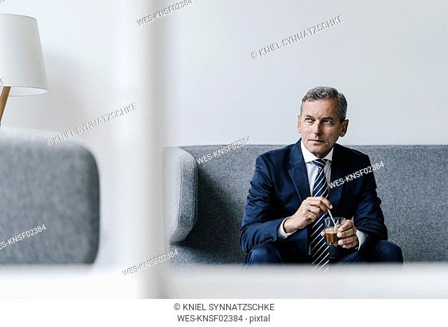 Mature businessman with glass of coffee sitting on couch in his office