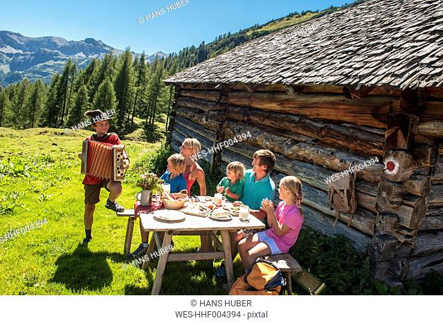 Austria, Salzburg Country, Family sitting outdoors enjoying boy playing accordion