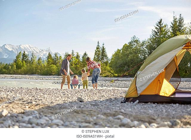 Rear view of family playing in river by tent, Wallgau, Bavaria, Germany