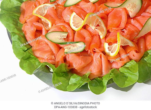 Non vegetarian Food , Fish Smoked Salmon (Rokt Lax in Swedish) surface texture clean and bone less , slices arranged in folded shapes with salad leave...