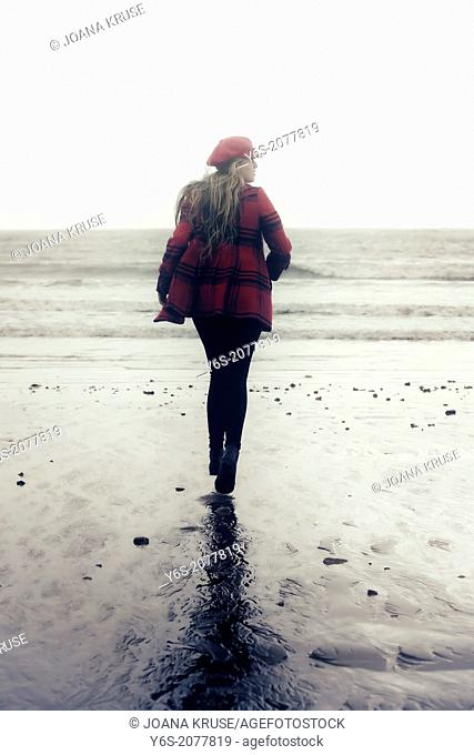 a girl in a red coat is running on a beach