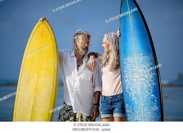 Affectionate senior couple with surfboards at beach