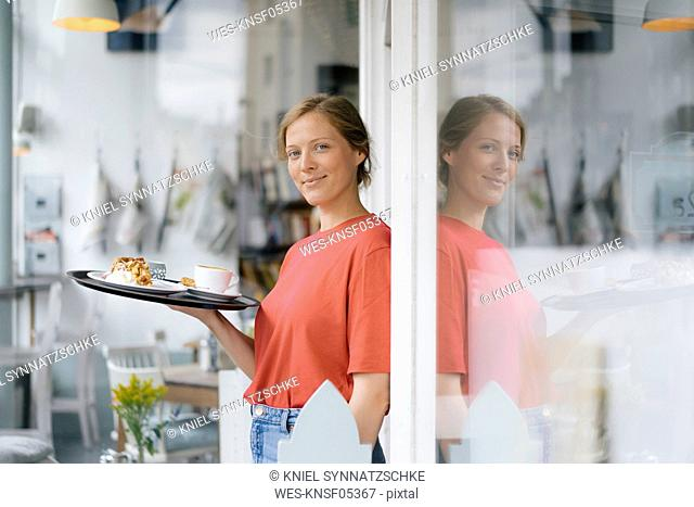 Portrait of smiling young woman serving coffee and cake in a cafe