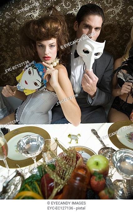Portrait of sexy couple with masquerade masks at dinner party