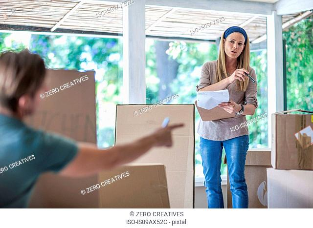 Moving house: couple organising cardboard boxes