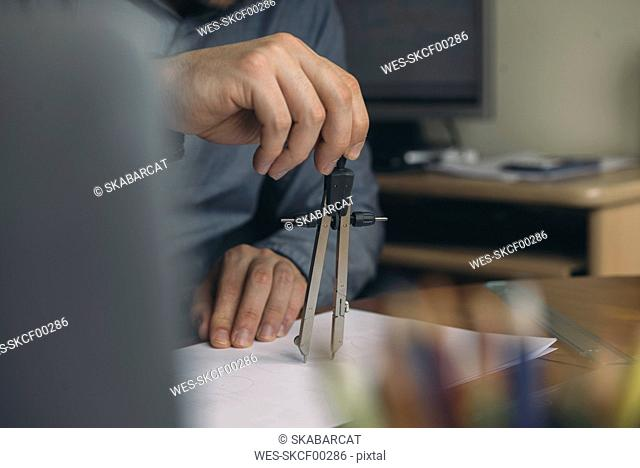 Close-up of man using compasses at desk