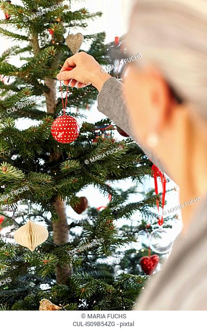 Senior woman putting bauble on christmas tree