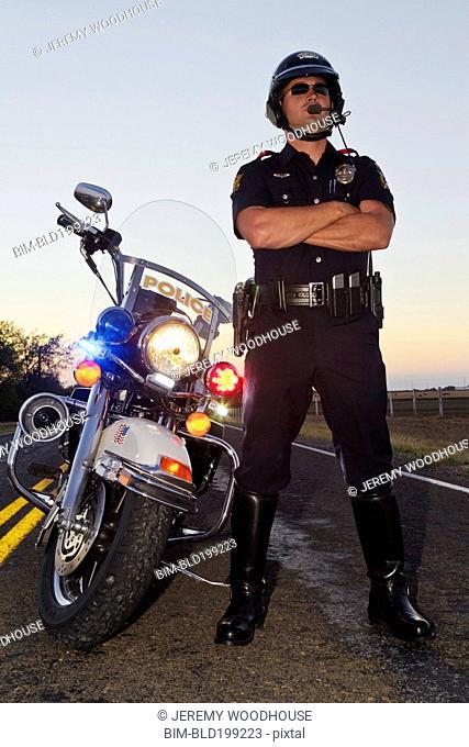 Caucasian policeman standing near motorcycle