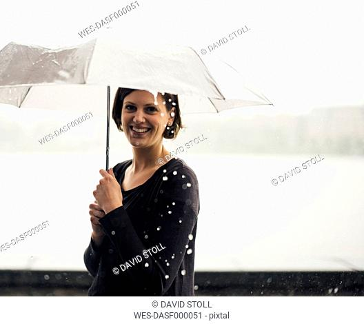 Portrait of smiling woman with umbrella on a rainy day