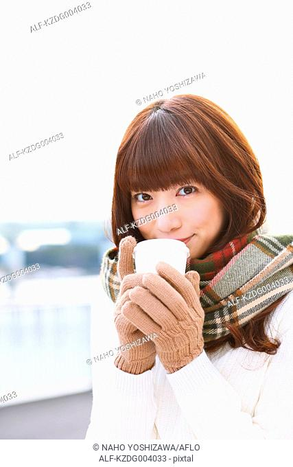 Attractive Japanese woman with coffee on a Winter day