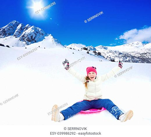 Happy girl sitting on sled with her hands lifted, wearing ski mask, in the mountains on sunny day