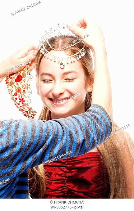 Girl with Blond Hair in Red Dress Fitting a Crown on her Head