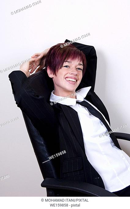 Happy businesswoman laying back on a chair
