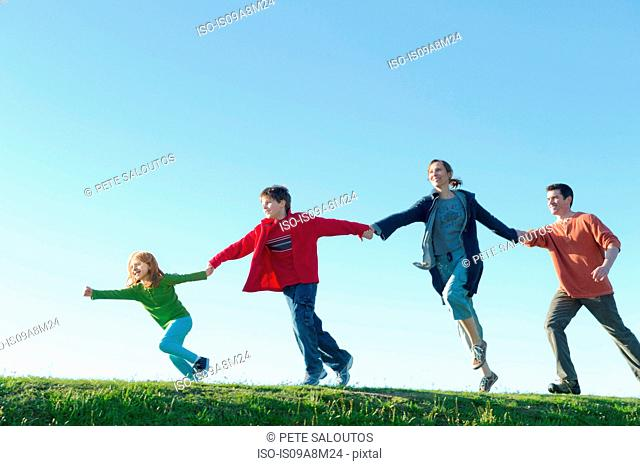 Parents and two children running and holding hands