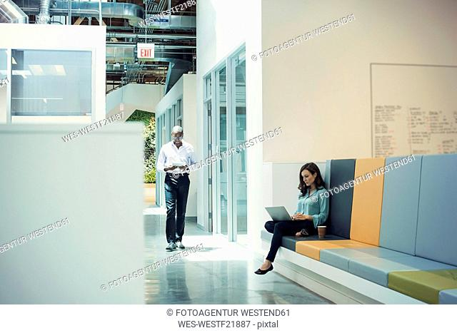 Woman working in lobby, colleague walking down corridor