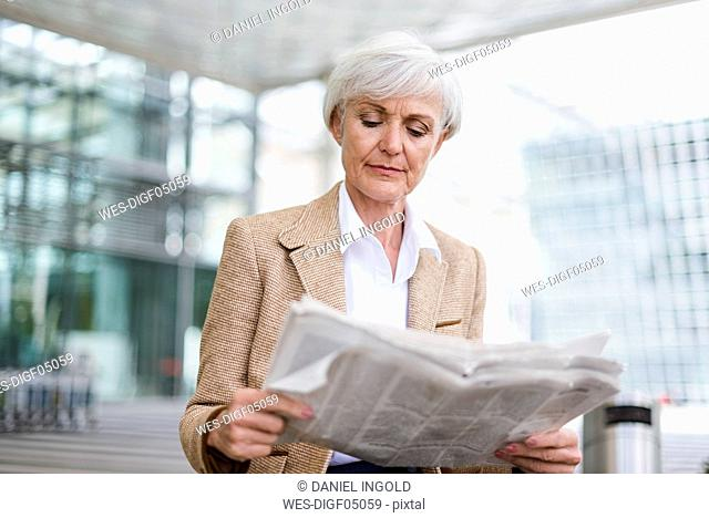 Senior businesswoman in the city reading newspaper