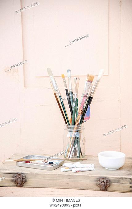Painting materials, glass jar with paint brushes, paint tubes and a bowl