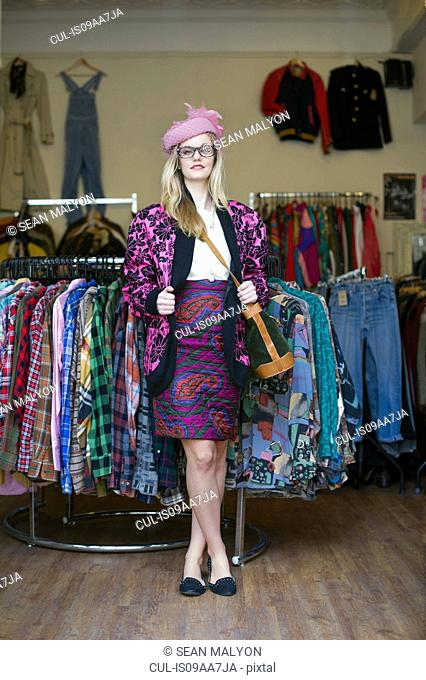 Woman standing in clothes shop wearing vintage clothes