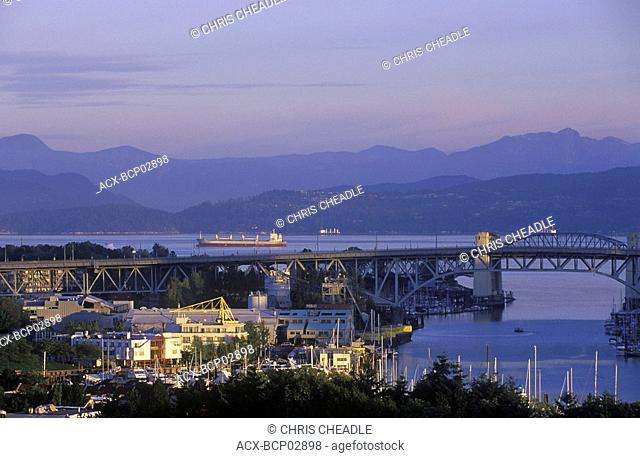 View to west across Granville Island to Burrard Bridge and freighters in Burrard Inlet, Vancouver, British Columbia, Canada